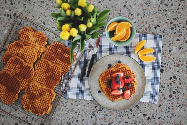 søtpotetvafler med bær og appelsin servert på bordet