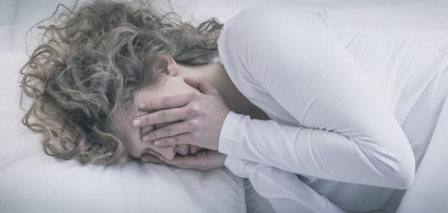 Kvinne i sengen trøtt og frustrert, kledd i hvitt