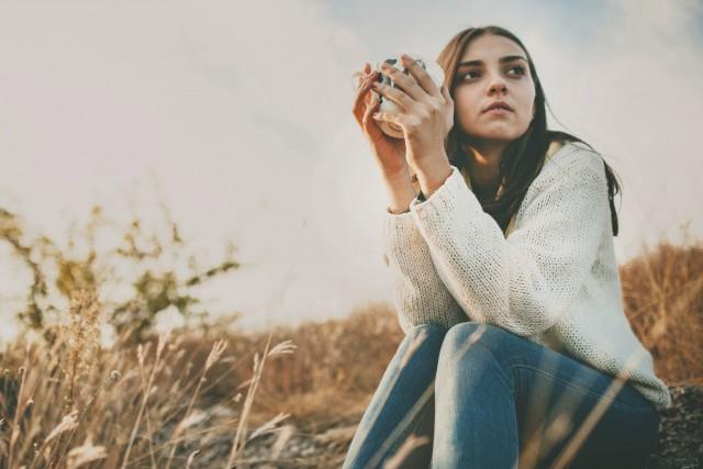 kvinne sitter ute i engen med en kaffe