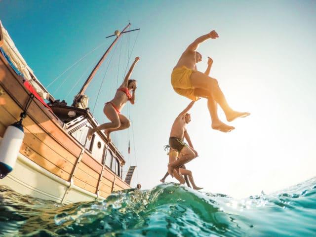 gjeng på båt som hopper i vannet, diabetesen på sommeren