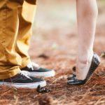 Føtter av en mann og en dame som står ute på gresset