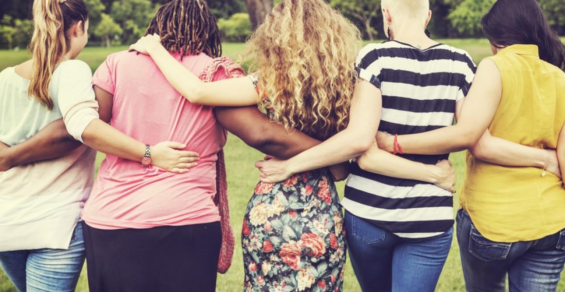 Kvinner ute holder rundt hverandre, arm i arm, samhold