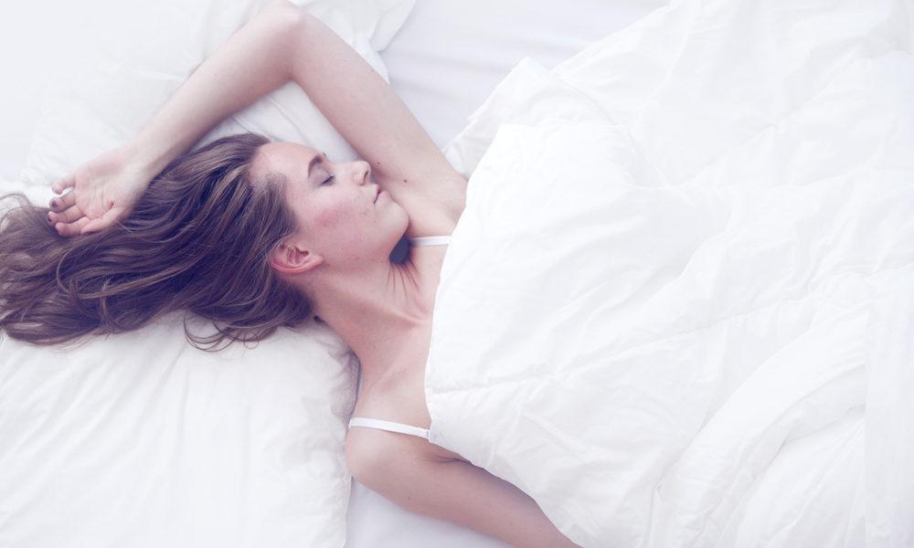 kvinne sover i senga hvite laken