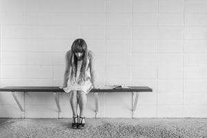 svart-hvitt foto av trist jente på en benk inne