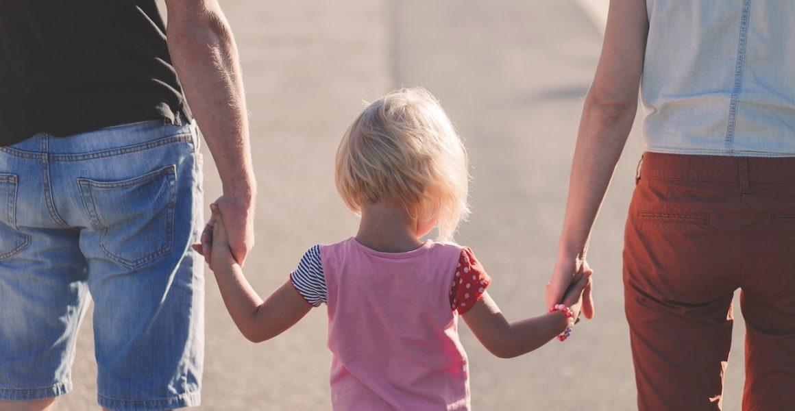 Far og mor holder hender med datteren