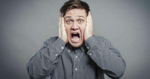 frustrert mann med hendene foran ørene