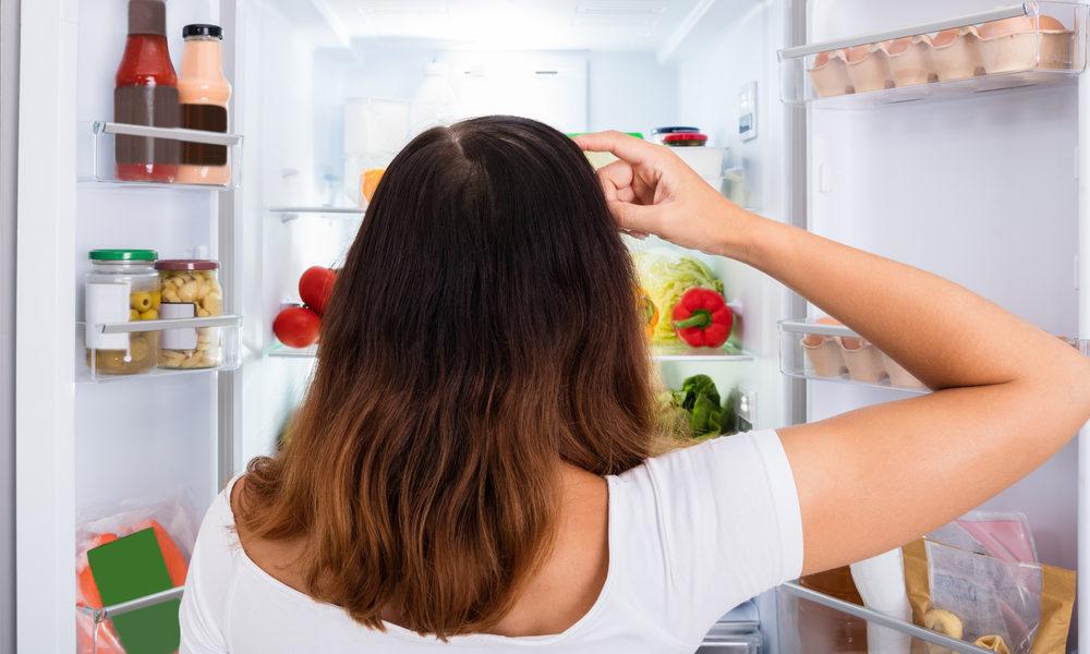 kvinne ser i kjøleskapet etter mat