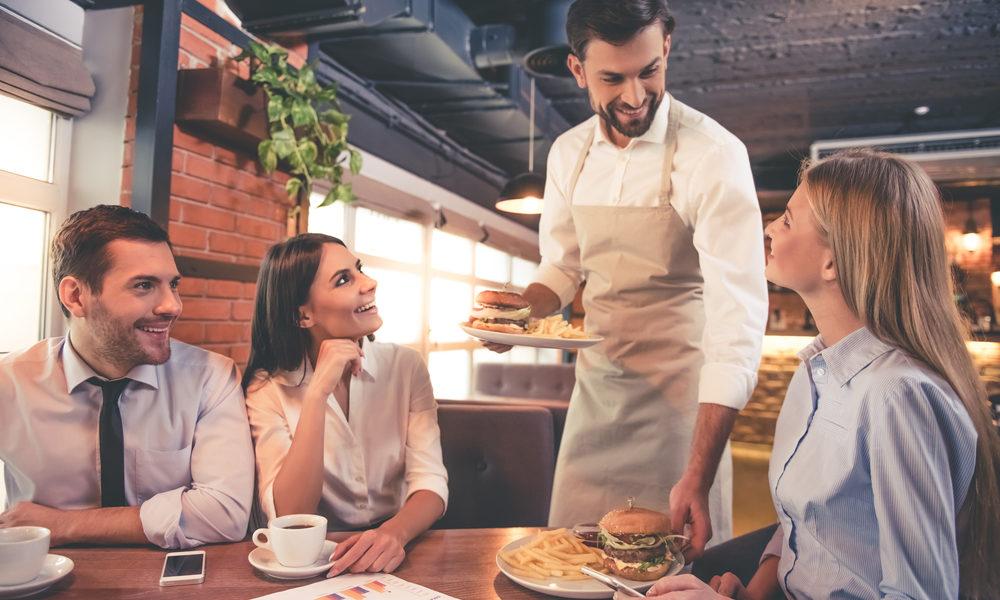 venner på restaurant, servitør serverer burger