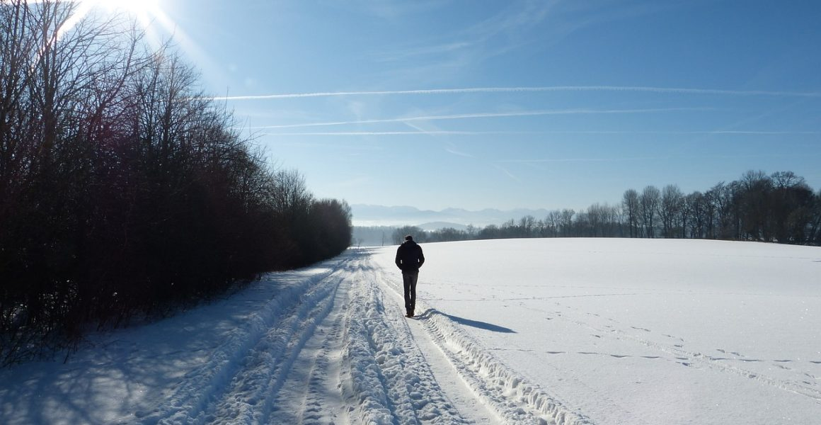 mann går alene i vinterlandskap