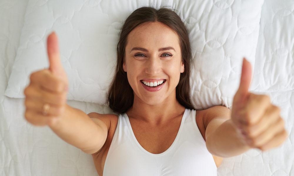 kvinne i sengen tomler opp fornøyd