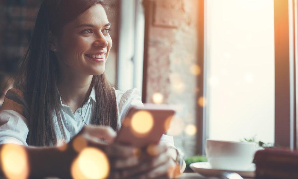 kvinne på kafé med mobiltelefon