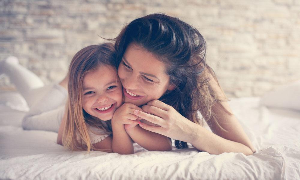 mor og datter glade i senga