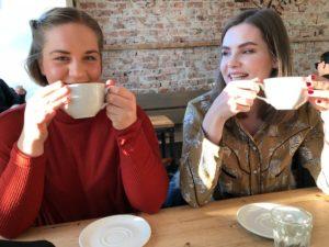 venninner på kafé ler og drikker kaffe