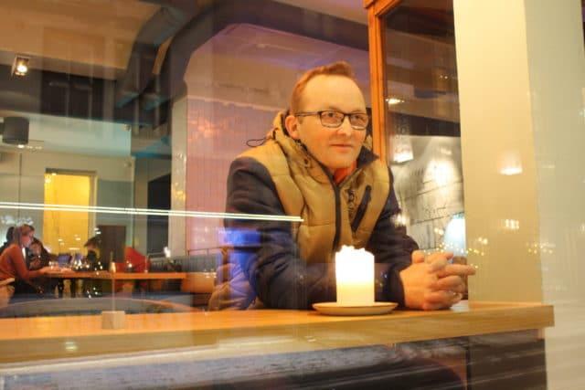 Kjell Arild ser ut vinduet på kafé, tankefull om dårlig samvittighet overfor familien