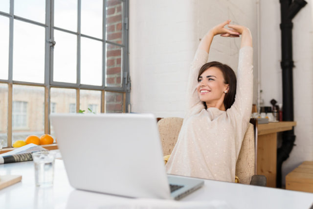 Fornøyd kvinne strekker seg på hjemmekontor, som er den nye «normalen»